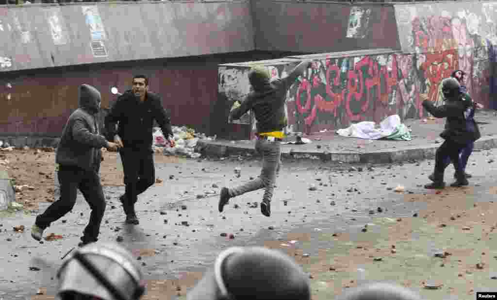 Riot police try to prevent protesters supporting Egyptian President Mohamed Morsi from throwing rocks at anti-Morsi protesters during clashes in Alexandria, Egypt, December 21, 2012.