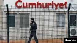 FILE - A private security employee stands guard at the entrance of the offices of daily newspaper Cumhuriyet, in Istanbul, Turkey.