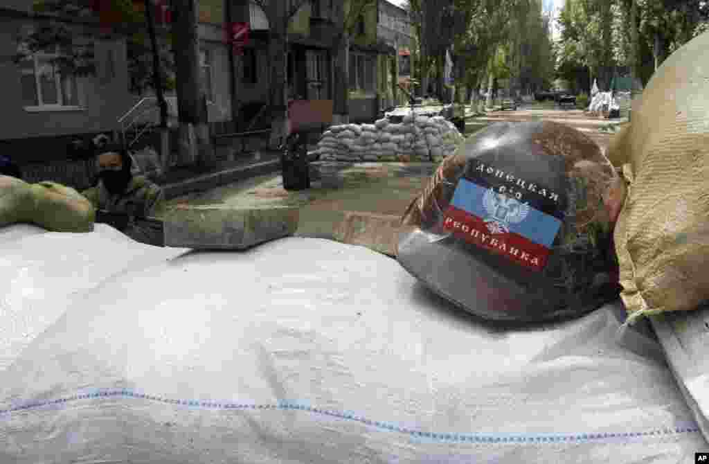 An armed pro-Russian man guards the local administration building behind barricades with helmet bearing a flag of self-proclaimed Donetsk People's Republic, Slovyansk, May 6, 2014.