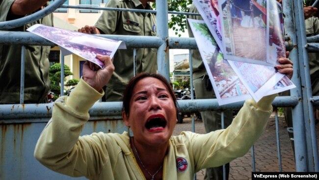 Bà Huỳnh Thị Hồng Loan kêu khóc với hình ảnh và giấy tờ khiếu kiện trên tay.