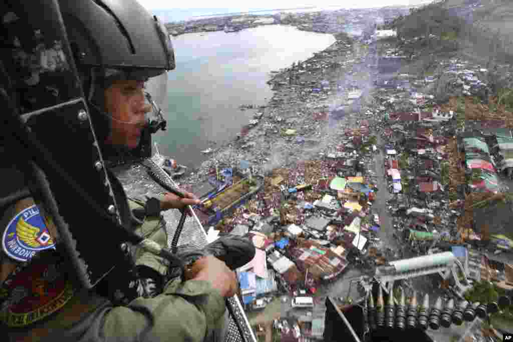 A Philippine Air Force crew looks out from his helicopter as Typhoon Haiyan-ravaged city of Tacloban is seen in the background, during a flight to deliver relief goods, Nov. 19, 2013.