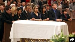 Family, including mother Roxanna Green, third from right, father John Green, second from right, and son Dallas Green, right, kneel in prayer behind the casket during the funeral of his daughter, 9-year-old Christina Taylor Green, in Tucson, Arizona, 13 Ja