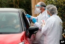 Medical staff test a person in their car with COVID-19 symptoms, at a drive-through testing site outside a medical biology laboratory in Anglet, southwestern France, Monday, April 20, 2020.