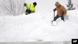 Mark Settlemyer, left, gets help clearing snow from the roof of his mother's house from Ken Wesley in Lancaster, N.Y., Nov. 19, 2014.