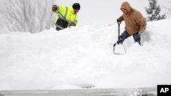紐約州連日降雪,民眾在屋頂清理厚雪。