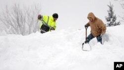 Dos hombres palean la nieve, no en una montaña en sí, sino sobre el techo de una casa.