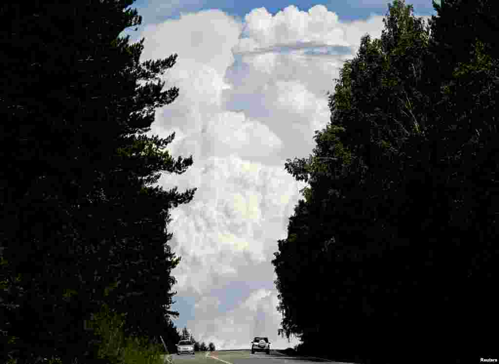 """Cars drive along the """"Yenisei"""" M54 federal highway, with heavy clouds seen in the sky, through the Siberian Taiga area outside Krasnoyarsk, Russia."""