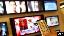 A visitor uses a remote control as she looks at television programmes during the annual MIPCOM television programme market in Cannes, southeastern France, October 4, 2010. The International film and programme market for TV, video, cable and satellite (MIP