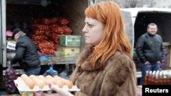 Seorang perempuan membawa telur menuju pasar yang buka seminggu sekali setiap Sabtu, di Stavropol, Rusia selatan, 7 Maret 2015. (Foto: dok).