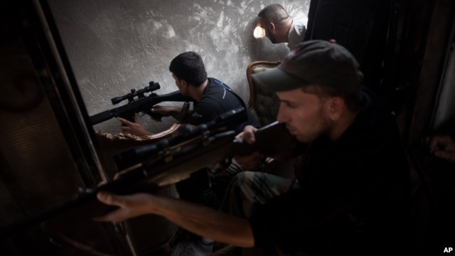 FSA soldiers scan for targets from within a bombed building in Saif Al Dula district in Aleppo, Syria, Monday, Sept. 10, 2012.