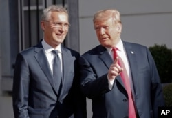 FILE - U.S. President Donald Trump, right, gestures as he speaks to the media prior to his bilateral breakfast with NATO Secretary-General Jens Stoltenberg, left, in Brussels, Belgium, July 11, 2018.