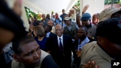 Former Haitian President Jean-Bertrand Aristide, center, smiles as he greets supporters outside the courthouse in Port-au-Prince, Haiti, March 20, 2017.