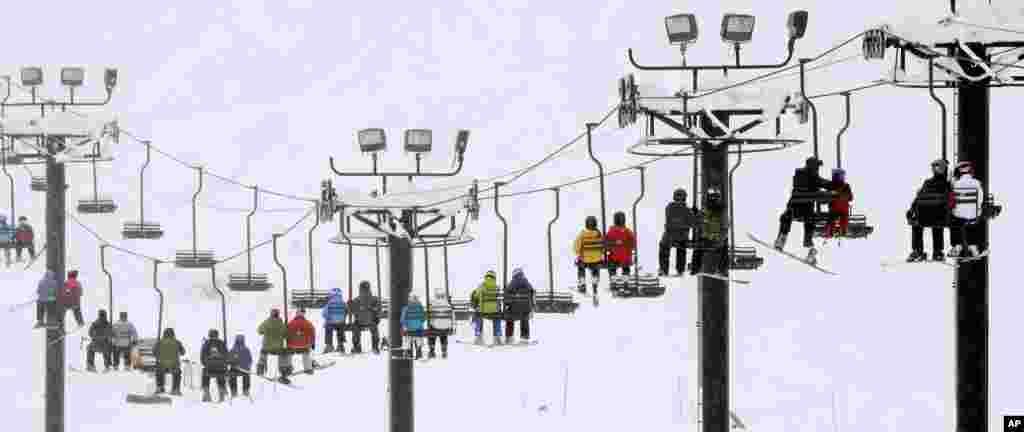미국 워싱턴수 수노콸미파스의 스키장에서 스키어와 스노우보더들이 리프트로 이동하고 있다.