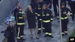 La primera ministra, Theresa May, observa lo que queda de la torre Grenfield en Londres, tras el mortal incendio en el que murieron al menos 17 personas.