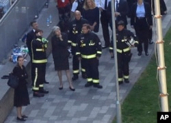 "Britain's Prime Minister Theresa May, center, speaks to firefighters after arriving at Grenfield Tower in London, June 15, 2017, following a deadly fire in the apartment block. She has been dubbed as ""Maybot"" for her often programmed or perfunctory responses."