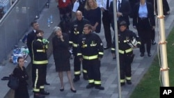 FILE - Britain's Prime Minister Theresa May, center, speaks to firefighters after arriving at Grenfell Tower in London, June 15, 2017, following a deadly fire in the apartment building.