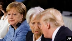 German Chancellor Angela Merkel watches as President Donald Trump talks with IMF Managing Director Christine Lagarde during the Gender Equality Advisory Council breakfast during the G-7 summit, June 9, 2018, in Charlevoix, Canada.