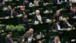 Iranian lawmakers attend an open session of parliament to choose the interim presiding board in Tehran, Iran, Sunday, May 29, 2016. Iran's long-serving parliament speaker Ali Larijani will retain his post despite gains by reformists in elections held earlier this year, the official IRNA news agency reported Sunday.