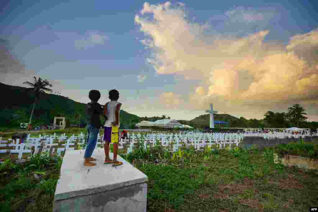Two young residents watch as people visit the mass graveyard for victims of super Typhoon Haiyan, which hit in 2013, in Tacloban City, Leyte province, central Philippines.