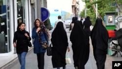 FILE - Iranian women make their way along a sidewalk in downtown Tehran, Iran, Apr. 26, 2016.