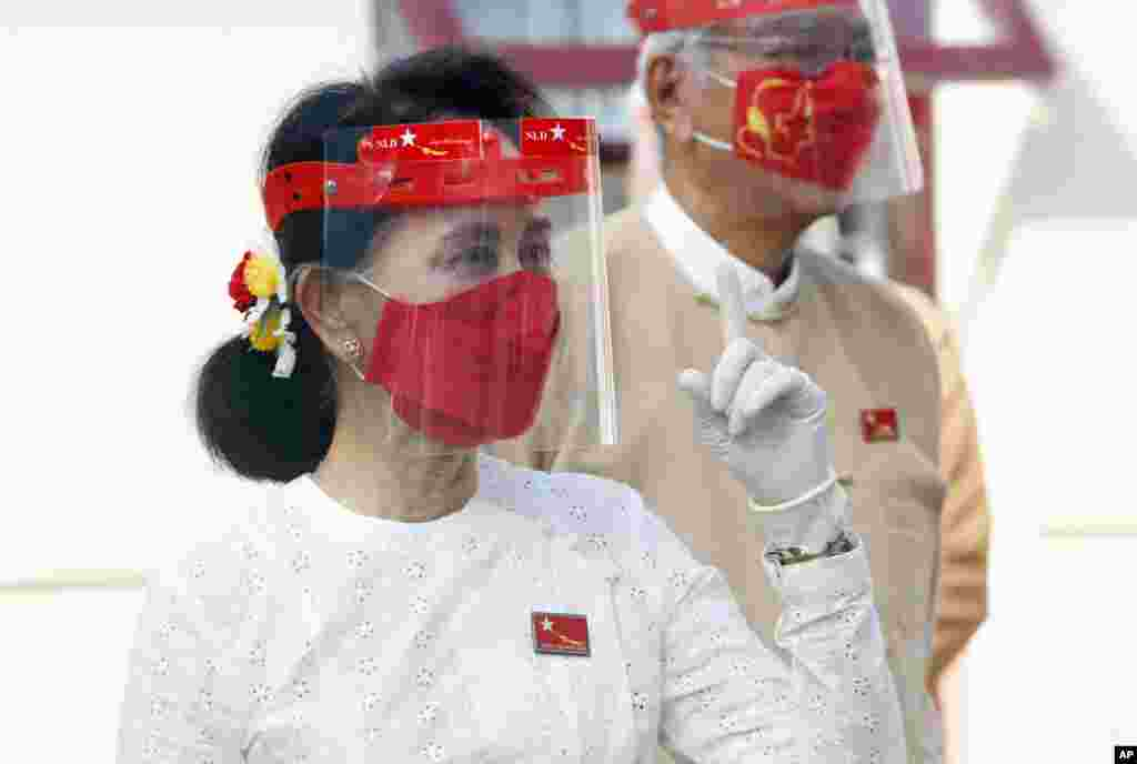 Myanmar leader Aung San Suu Kyi wearing a face shield, mask and gloves, is seen during a flag-raising ceremony to mark the first day of election campaign at the National League for Democracy party's temporary headquarters in Naypyitaw.