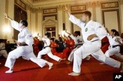 共和党众议员尼克·史密斯(左)和民主党众议员小杰西·杰克逊在参加李峻九大师在国会考核颁发跆拳道黑带的活动之前热身。(2001年7月23日)