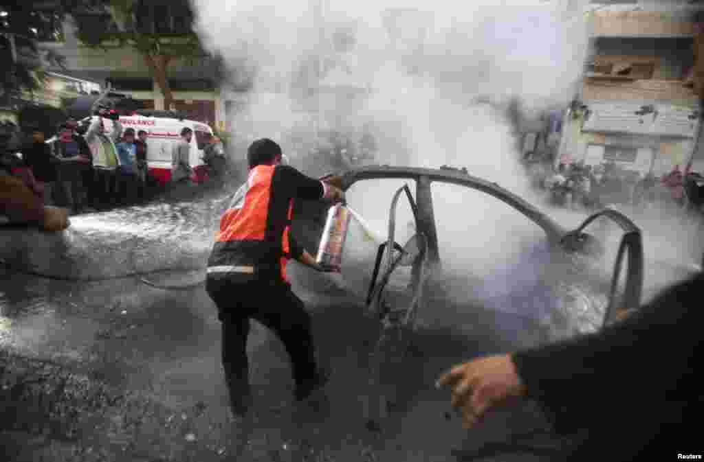 Palestinians extinguish a fire after an Israeli air strike on a car carrying Hamas military chief Ahmed al-Jaabari, Gaza City November 14, 2012.