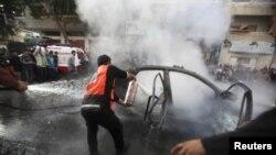 Filistinliler Hamas komutanının yanan aracını söndürmeye çalışırken
