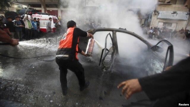 Palestinos extinguen el fuego luego que un misil israelí destruyó el carro en el que viajaba el jefe militar de Hamás, Ahmed al-Jaabari, en la ciudad de Gaza, este miércoles 14 de noviembre de 2012.