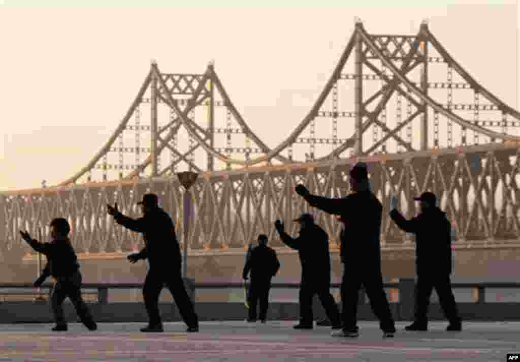 "Chinese people perform a morning exercise with a backdrop of Friendship Bridge linking between China and North Korea, in Dandong, China, Friday, Nov. 26, 2010. Chinese Premier Wen Jiabao responded by calling on all sides to show ""maximum restraint"" and pu"