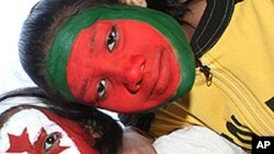 Two school children with their faces painted in the colors of the national flags of the countries participating in the upcoming Cricket World Cup in the northern Indian city of Lucknow.