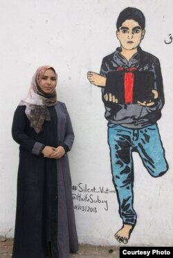 Yemeni artist Haifa Subay stands in front of one of her murals in the Yemeni capital, Sanaa. The mural shows a boy holding a leg he lost in a land mine explosion — one of the issues Subay wants to shed light on.