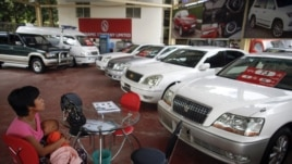 A potential customer breastfeeds her baby a saloon for newly imported cars in Rangoon.
