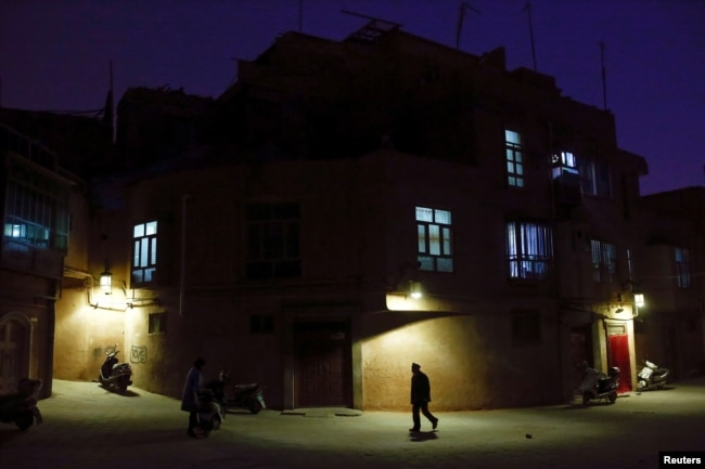 "A man walks along a street at night in the old town of Kashgar, Xinjiang Uighur Autonomous Region, China, March 23, 2017. Thousands of ""convenience police stations"" have been built across Xinjiang. They are typically just hundreds of meters apart in what party boss Chen Quanguo calls a ""grid-style social management system."""