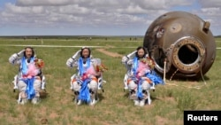 Astronauts (L-R) Zhang Xiaoguang, Nie Haisheng and Wang Yaping salute after returning to earth in the re-entry capsule of China's Shenzhou-10 spacecraft at its main landing site in north China's Inner Mongolia Autonomous Region, June 26, 2013.