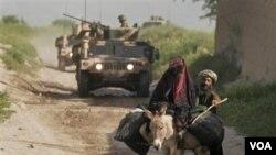 Konvoi pasukan NATO saat melakukan patroli di wilayah pedalaman, sementara seorang wanita Afghanistan menaiki keledai dengan didampingi suaminya.