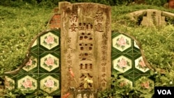 The ornate tile detail on one of the many overgrown graves at Singapore's Bukit Brown Cemetery. (VOA/K. Lamb)