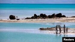 Trẻ em trên đảo South Tarawa, nước Cộng hòa Kiribati. Quốc gia này gồm 33 đảo san hô chỉ cao hơn mực nước biển 1 mét. Với tình trạng mực nước biển dâng lên, Tổng thống nước này tiên đoán nước ông sẽ không còn người ở trong 30 đến 60 năm vì nước ngập và ô nhiễm nguồn cung cấp nước ngọt