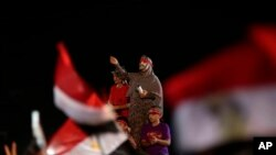 قاہرہ کے ایک مظاہرے میں معزول صدر محمد مرسی کی حامی ایک خاتون ماسک پہنے فوج کے خلاف نعرے لگارہی ہیں