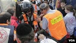 En las cercanías de la estación de autobuses de Jerusalén, rescatistas y paramédicos trasladan a uno de los heridos.