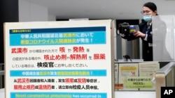 日本成田國際機場的工作人員在調整體溫監測儀以測試從中國武漢和其他城市抵達的旅客健康狀況。 (2020年1月23日)