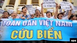 Vietnamese protesters hold a large banner reading 'Vietnam People Save The Sea' during a rally denouncing recent mass fish deaths in Vietnam's central province, in Hanoi, Vietnam, May 1, 2016.