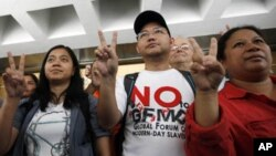 Eman Villanueva (C), vice chairperson of the Filipino Migrant Workers Union, along with other representatives, shows a victory sign after a court ruling in favor of foreign domestic workers seeking permanent residency, Hong Kong September 30, 2011.