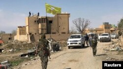 FILE - A Syrian Democratic Forces flag flutters on a damaged building in the town of Baghuz, Syria, March 23, 2019.