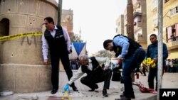 Les agents de la sécurité égyptienne et la police judiciaire inspectent le site d'une attaque à l'arme à feu à l'extérieur d'une église au sud de la capitale du Caire, le 29 décembre 2017.