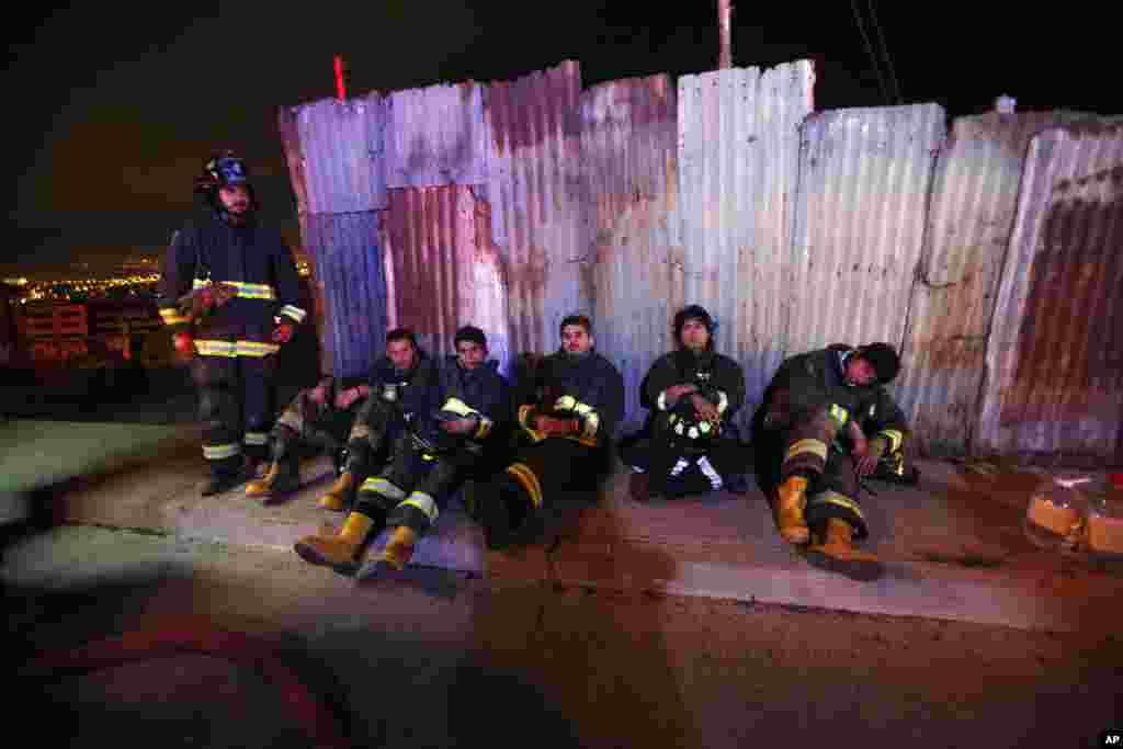 Bombeiros fazem um pequeno intervalo de descanso após horas a combater o fogo que alcançou áreas urbanas em Valparaiso, Chile, Abril 14, 2014.