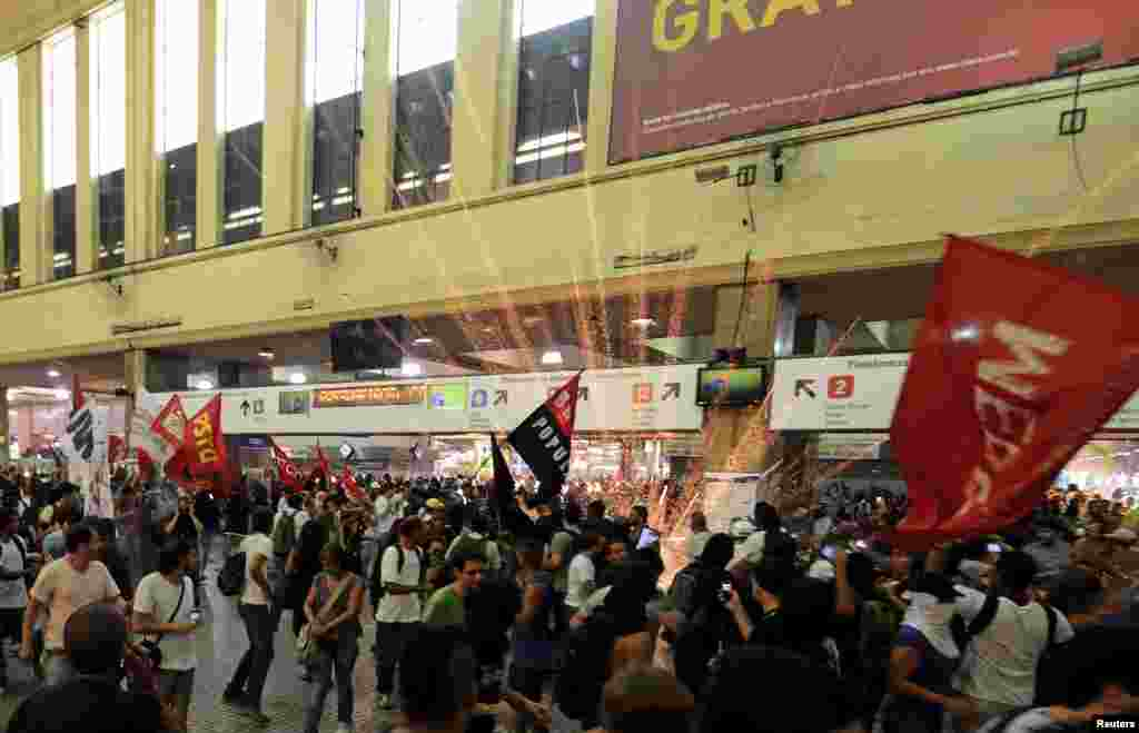 """A firework explodes as members of the """"Free Pass"""" movement invade the Central Train Station to demand zero tariffs in the Brazilian public transport system in Rio de Janeiro, Feb. 6, 2014."""