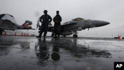 美国海军乔治华盛顿号航空母舰停靠在香港,舰上人员站在一架F/A-18战斗机前(2011年11月9日)