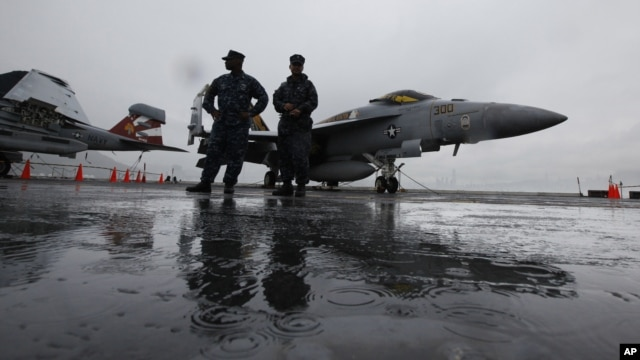 U.S. Navy deck crew members stand in front of an F/A-18 fighter jet on the aircraft carrier USS George Washington in Hong Kong, November 9, 2011.