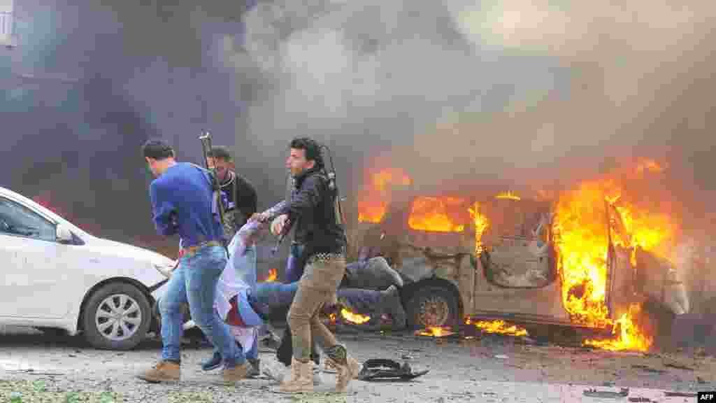 A handout picture released by the official Syrian Arab News Agency (SANA) shows Syrians carrying an injured man after a powerful car bomb exploded near the headquarters of Syria's ruling Ba'ath party in the center of Damascus, February 21, 2013.